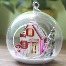Nádherná vánoční dekorace. Skleněná koule se dřevěným domečkem uvnitř.